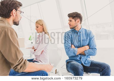 Serious woman is taking offense at man beside her and crossing hands. Anxious man sitting near