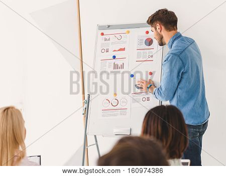 Serious lector is standing near blackboard and absorbedly reading information
