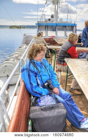 ONEGA LAKE RUSSIA - August 10.2008: Woman with camera on the top deck of the pleasure boat looking into the distance
