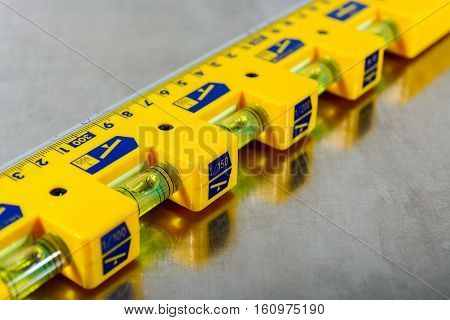 yellow construction level on stainless steel background