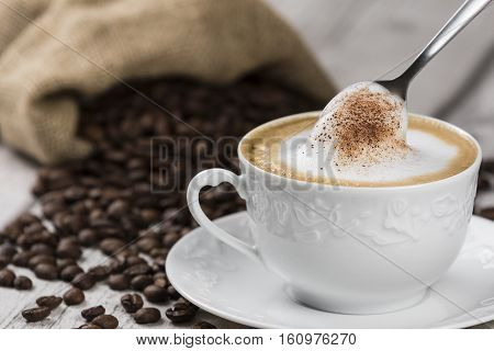 Cappuccino Coffee Cup and Spoon / Composition of Cup of Cappuccino and spoon with foam, sack of coffee beans on white wooden table