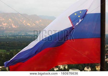 Slovenian national flag fluttering over Lake Bled and town