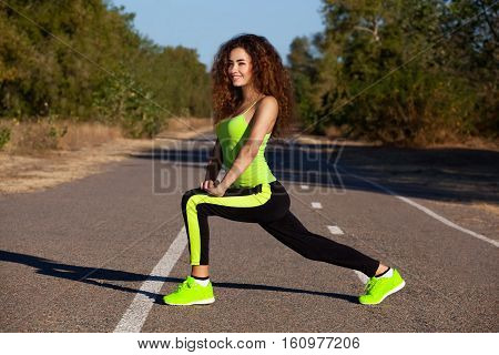 Young attractive athletic girl in black-green tracksuit doing morning sports training in the park.