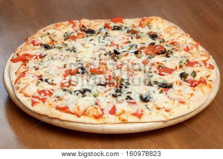 Cheeze pizza on a round wooden board on table, closeup