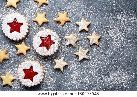 Christmas or New Year homemade cookies star with strawberry jam. Flat lay.Traditional Austrian christmas cookies - Linzer biscuits filled with red strawberry jam. Top view. Copy space.