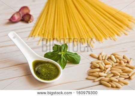 Closeup of pesto genovese sauce and linguine pasta pine nuts and garlic on a table