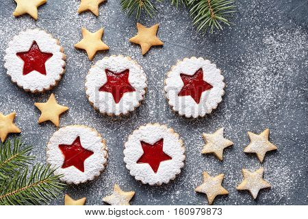 Assorted cookies. Christmas festive homemade ginger cookies star with strawberry jam. Flat lay. Shortcrust pastry. Traditional Austrian Linzer cookie on green background. Top view.
