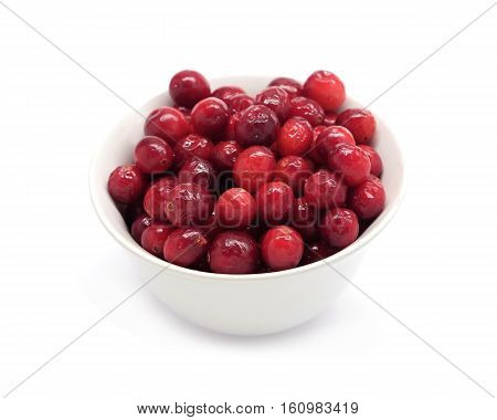 Cranberries in round white bowl isolated on white background top view close up