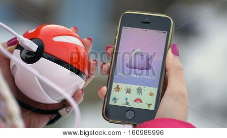 Samara, Russia - December 8, 2016: woman playing pokemon go on his iphone. pokemon go multiplayer game with elements of augmented reality. Catching the Ditto pokemon.