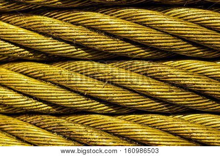 Industrial abstract background. Yellow Steel cable close-up photo. New rope lubrication.