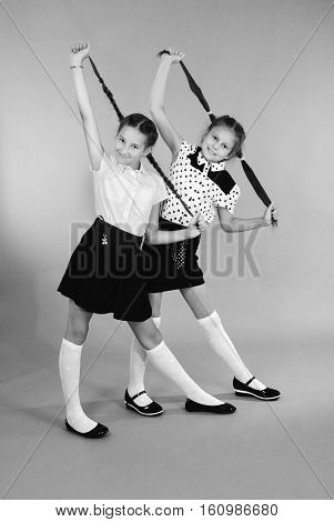 Two school girls plays with plaited hair. Two lovely girls holds plaits of hair in hands and looks in the camera. Black and white image