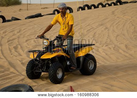 DUBAI, UAE - APRIL 20 2012: Desert safari camp staff riding an ATV (All Terrain Vehicle). ATV rides are offered to tourists as part of the camp experience.