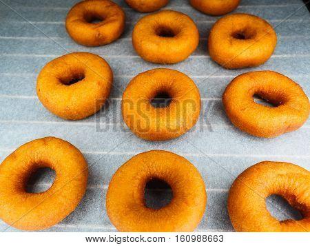 Closeup Of Freshly Made Dark Brown Doughnuts On Baking Paper