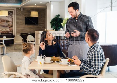 Friendly smiling waiter taking order at table of family having dinner together.