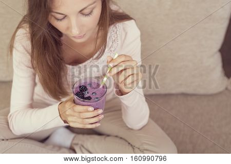 Beautiful girl sitting on a living room couch smiling and holding a glass of raspberry and blueberry mix smoothie. Focus on the smoothie