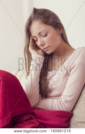Young woman sitting on a couch holding her head having a migraine