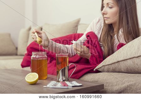 Sick woman lying in bed with high fever and a flu putting some honey in her tea. Lemon honey jar and pills set around the table focus on the honey