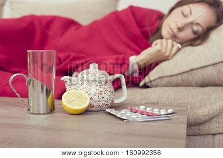 Sick woman covered with a blanket lying in bed with high fever and a flu resting. Teapot pills and lemon on the table focus on the lemon and a teapot