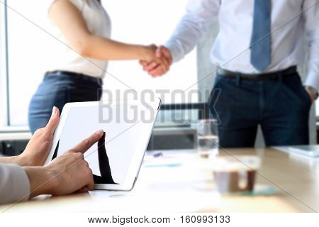 Business partners handshaking over business objects on workplace. businesswoman working with digital tablet