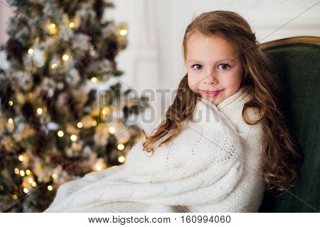 Cute little girl sits by the christmas tree, wrapped in a warm blanket at home.