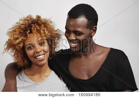 Stylish African Couple Posing In Studio: Happy Handsome Man In Black T-shirt Hugging His Beautiful G