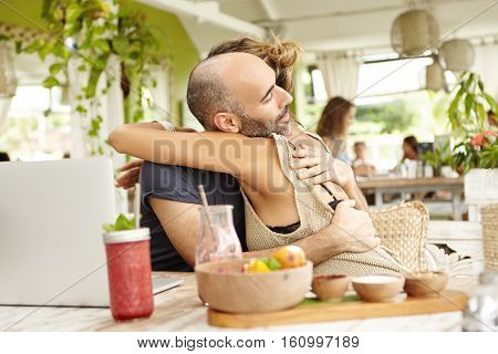 Sweet Moment Of Two Best Friends Hugging, Sitting At Cafe Table With Open Laptop And Drinks. Attract