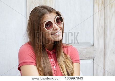 Headshot Of Flirty Young Female Wearing Fashionable Shades Having Playful Look And Cute Shy Smile Wh