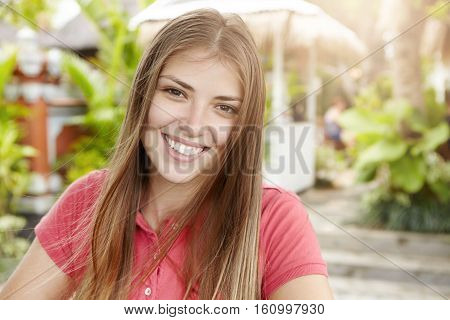 Beautiful Young Woman With Long Fair Hair Dressed In Polo Shirt Looking And Smiling At Camera With H