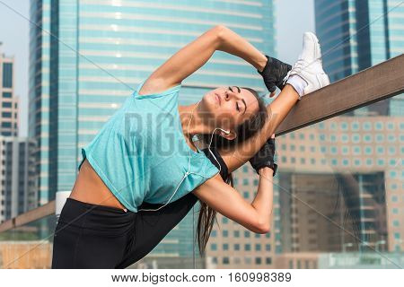 Young fitness woman doing standing split exercise on the city street. Sporty fit girl working out outdoors stretching her legs.