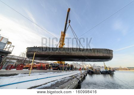 MOSCOW, RUSSIA - NOVEMBER 11, 2016: State Unitary Enterprise Mosvodostok performs recovery vessels on coastal winter parking. Easy river barge suspended in the automobile crane.