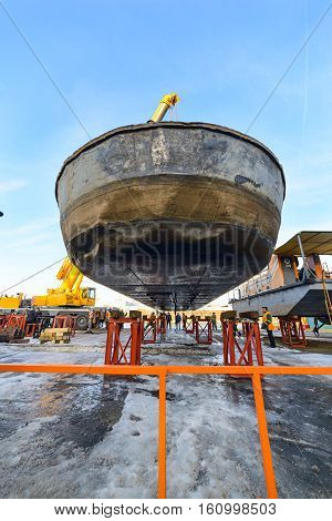 MOSCOW, RUSSIA - NOVEMBER 11, 2016: State Unitary Enterprise Mosvodostok performs recovery vessels on coastal winter parking. Barge hanging over metal supports.