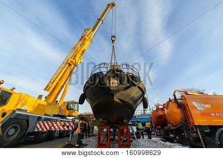 MOSCOW, RUSSIA - NOVEMBER 11, 2016: State Unitary Enterprise Mosvodostok performs recovery vessels on coastal winter parking. Truck Crane sets the ship on steel supports.