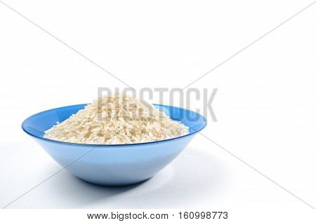 handful of long-grain rice isolated in the blue cup on left
