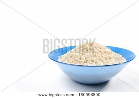 handful of long-grain rice isolated in the blue cup on right