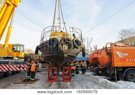 MOSCOW, RUSSIA - NOVEMBER 11, 2016: State Unitary Enterprise Mosvodostok performs recovery vessels on coastal winter parking. Workers take a river boat on the winter parking place.