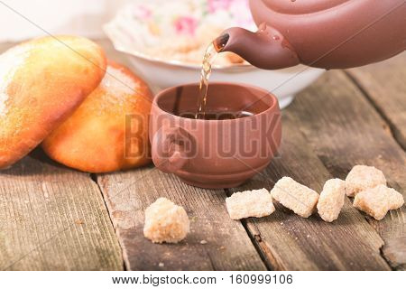 Some tea is given in a cup. The ceramic cup costs on an old wooden table. In a shot a part of a teapot and a stream of the given some tea pieces of sugar and pies