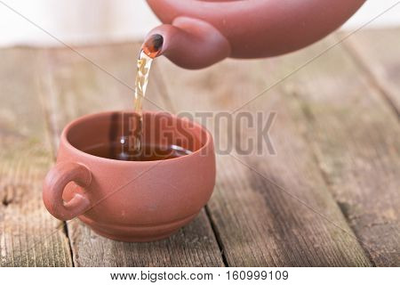 Some tea is given in a cup. The ceramic cup costs on an old wooden table. In a shot a part of a teapot and a stream of the given some tea