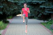 Sportive woman stretching before running. Sportive girl exercising outdoors. poster