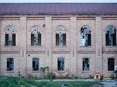 Picture of an abandoned building. The wall of the building made of red bricks. The windows of the building are broken. Green grass and kennel with dog before the wall of the building. poster