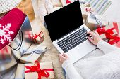 Christmas online shopping top view. Female buyer makes order on laptop computer, copy space on screen. Woman buy presents, prepare to xmas, among gift boxes and packages. Winter holidays sales poster