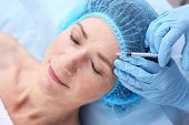 Senior woman having hyaluronic acid injection at beauty salon poster