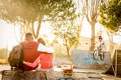Multiracial couple in love sitting at skate park with music watching friends on bmx freestyle exhibition - Urban relationship concept with young people having fun outdoors - Warm contrasted filter poster