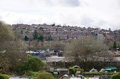 Stoke-on-Trent hillside, with terraced and semi-detached houses, car park, and allotments poster