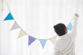 Portrait of Asian girl decorate he room with pastel bunting