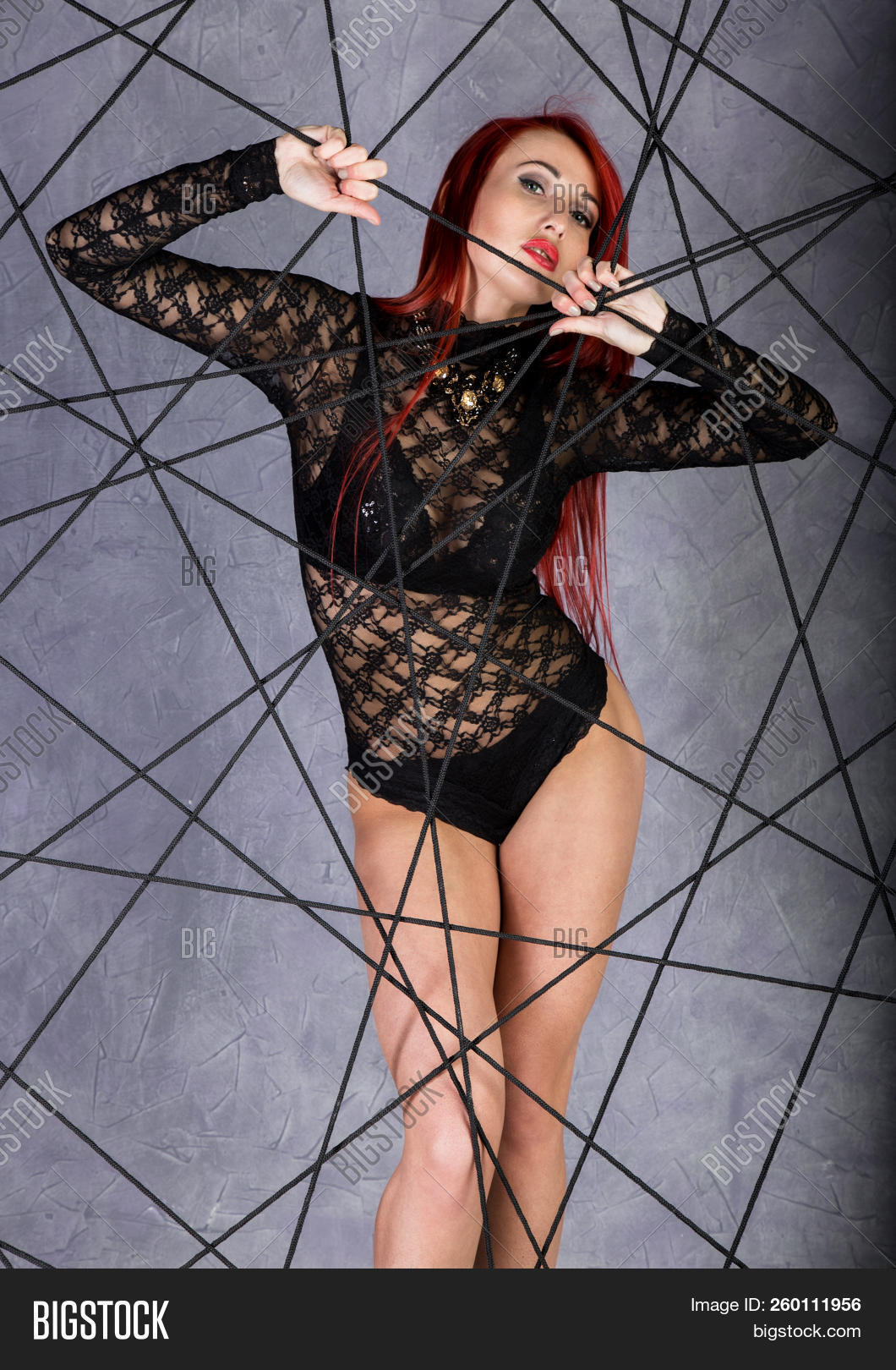 Young Sexy Woman Entangled In Ropes Web On A Gray Background
