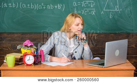 Teacher Woman Sit Table Work Laptop Surfing Internet Chalkboard Background. Organize Class And Make