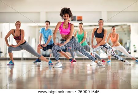 Pretty fitness trainer show aerobic exercises to fitness group