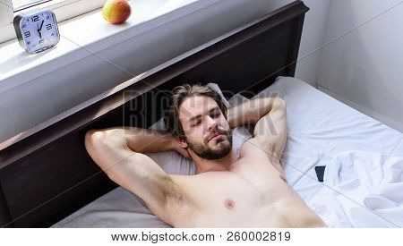 Man sleepy drowsy unshaven bearded face having rest. Pleasant relax concept. Let your body feel comfortable. Man unshaven handsome guy naked torso relaxing bed. Guy sexy macho lay white bedclothes poster