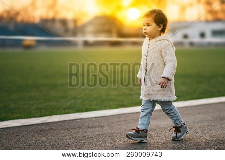 Cute Beautiful Girl Toddler Walking On The Street On Green Grass And Sunset Background. Happy Child
