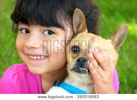 Hispanic girl holding and covering the eye of her chihuahua